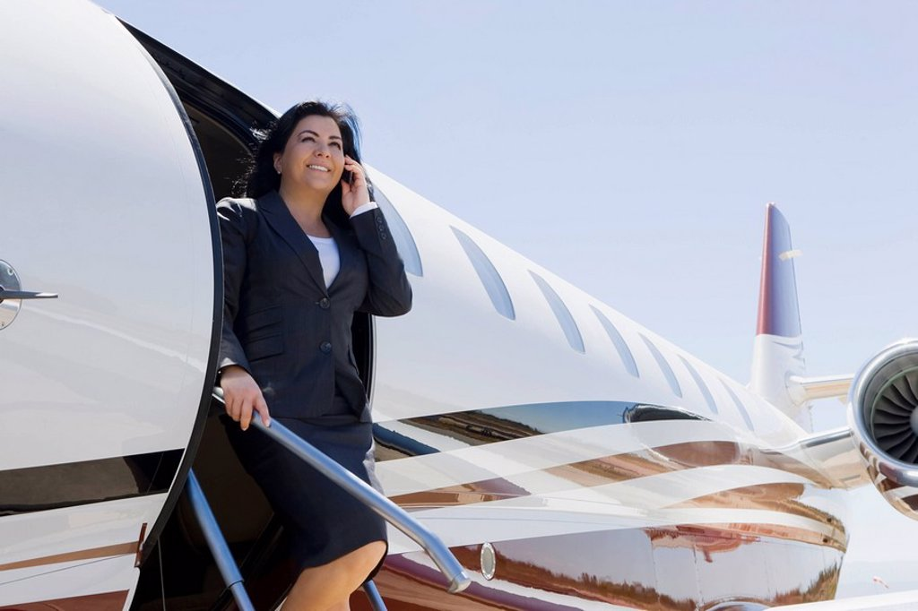 Hispanic businesswoman exiting private jet : Stock Photo