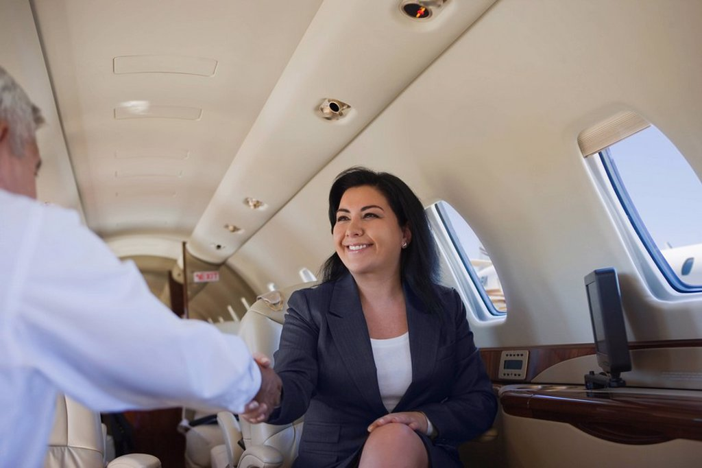 Stock Photo: 1589R-134060 Business people shaking hands on private jet