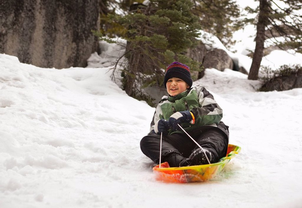 Stock Photo: 1589R-134621 Smiling Hispanic boy riding sled in snow