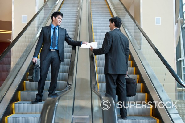 Businessman handing paperwork to co_worker on escalator : Stock Photo