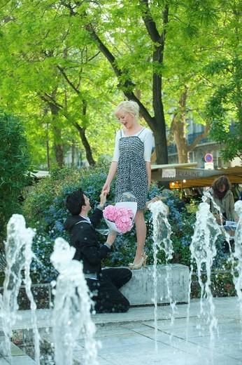 Caucasian man proposing to girlfriend near fountain : Stock Photo