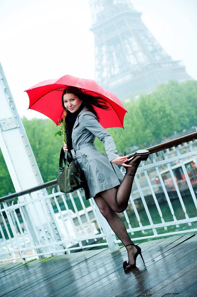 Stock Photo: 1589R-134806 Caucasian woman in high heel shoes with red umbrella near Eiffel Tower