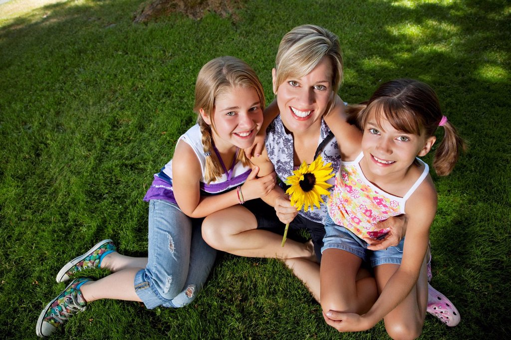 Stock Photo: 1589R-134816 Caucasian mother and daughters sitting grass
