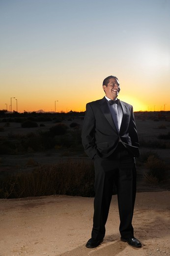 Smiling man in tuxedo standing in desert at sunset : Stock Photo