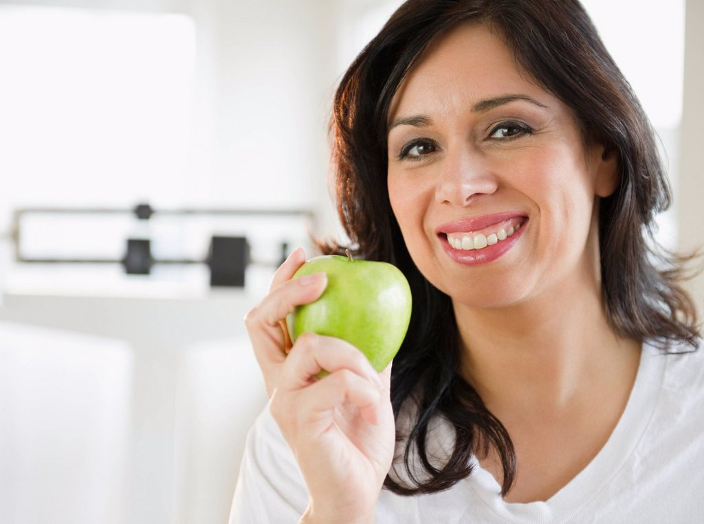 Stock Photo: 1589R-134891 Smiling Hispanic woman holding a green apple