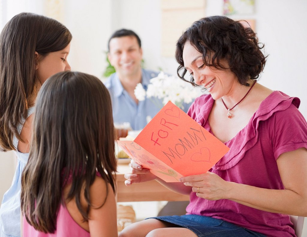 Stock Photo: 1589R-134896 Daughters giving mother Mother´s Day card