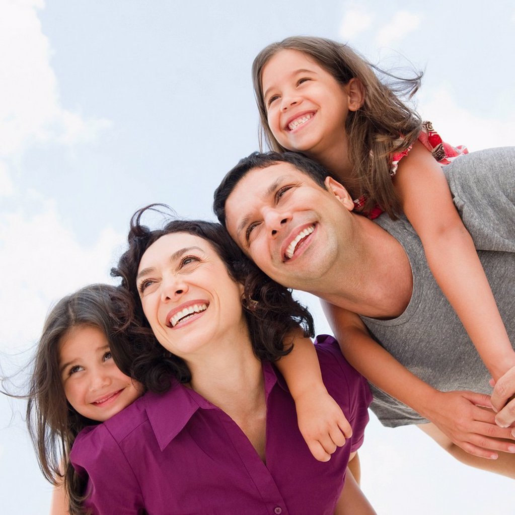 Smiling parents giving daughter´s piggyback ride : Stock Photo