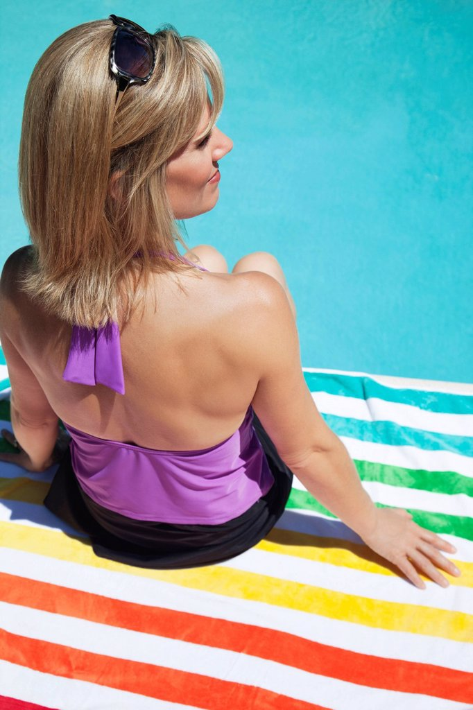 Stock Photo: 1589R-134972 Caucasian woman sitting near swimming pool