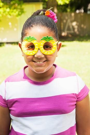 Smiling Hispanic girl wearing pineapple sunglasses : Stock Photo