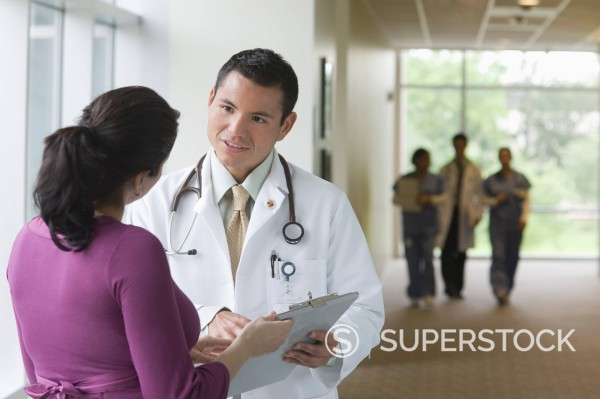 Stock Photo: 1589R-134987 Hispanic doctor talking to co_worker in hospital corridor