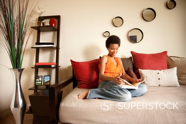 Woman sitting on sofa and reading book : Stock Photo