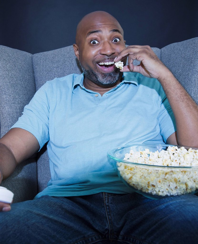 African American man eating popcorn and watching television : Stock Photo