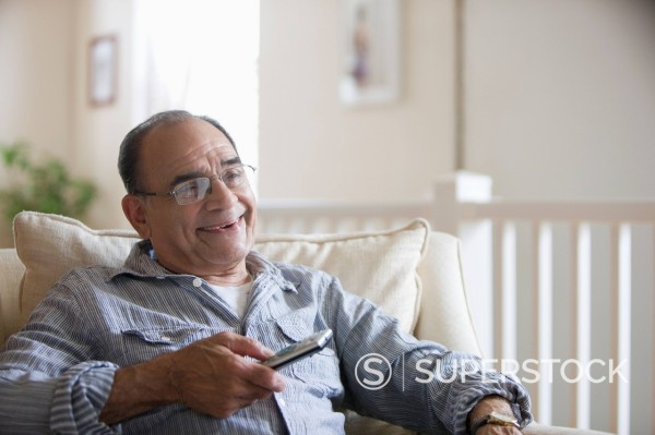 Stock Photo: 1589R-135075 Senior Hispanic man using remote control