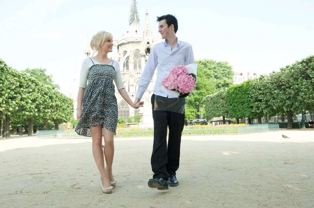 Caucasian couple holding hands in park near Notre Dame : Stock Photo