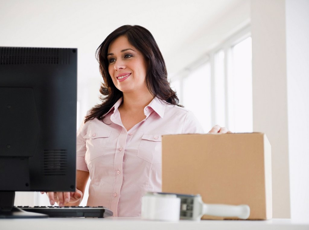 Smiling Hispanic woman with cardboard box using computer : Stock Photo