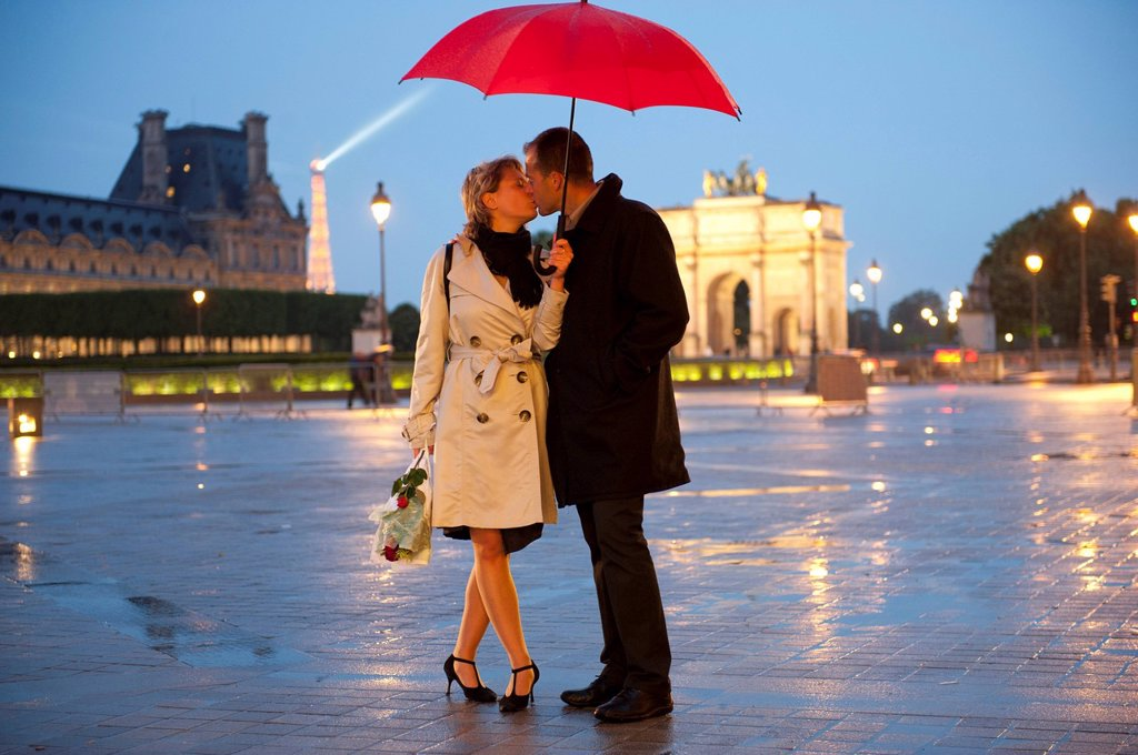 Stock Photo: 1589R-135437 Caucasian couple kissing in rain at night near the Louvre