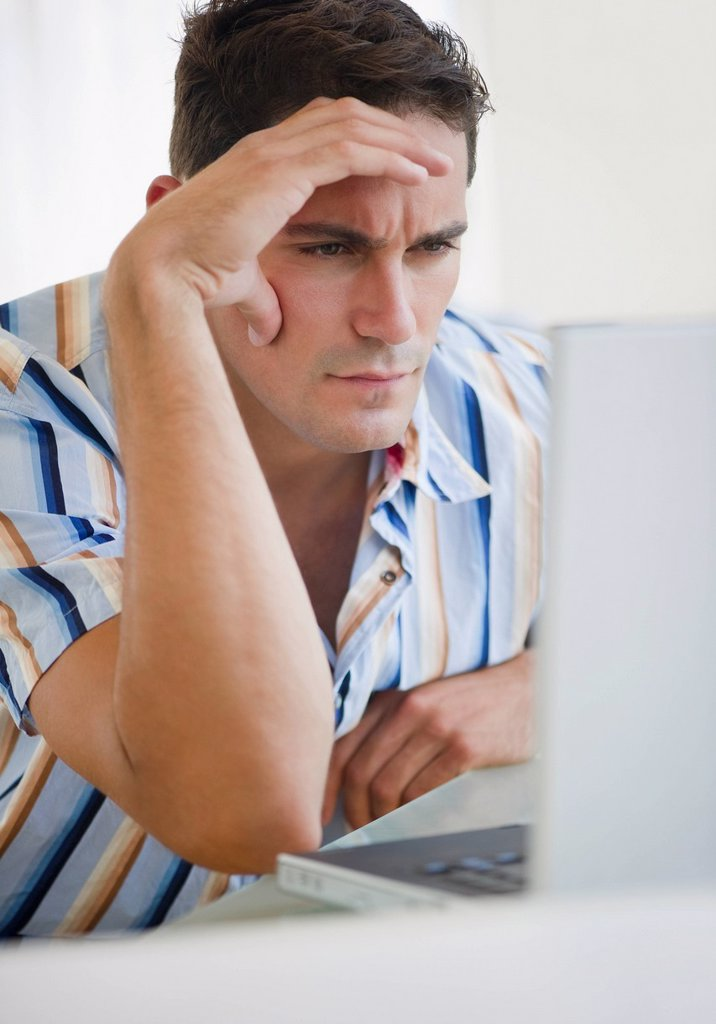 Frustrated mixed race businessman frowning at laptop : Stock Photo