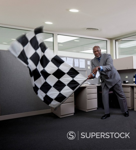 African American businessman waving checkered flag in office : Stock Photo