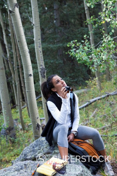 Hispanic woman using binoculars in forest : Stock Photo
