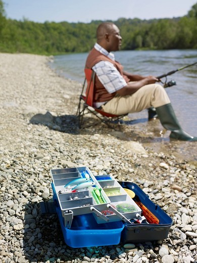 Stock Photo: 1589R-135997 Black man with tackle box fishing in stream