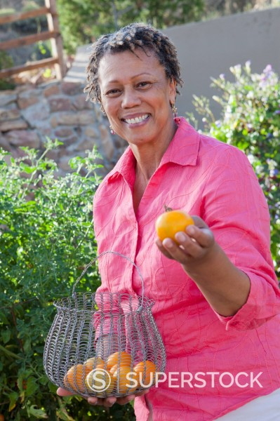Black woman holding basket of oranges : Stock Photo