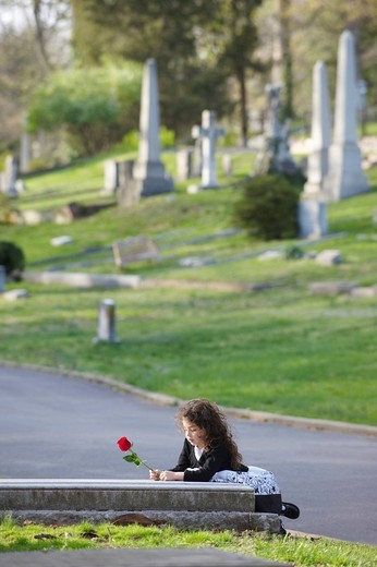 Stock Photo: 1589R-136535 Hispanic girl with rose visiting cemetery