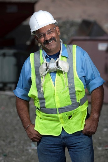 Hispanic sanitation worker in recycling plant : Stock Photo