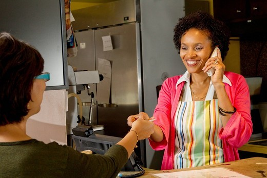 African American bakery owner taking customer´s credit card : Stock Photo