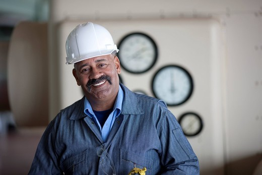 Smiling Hispanic worker in hard_hat : Stock Photo