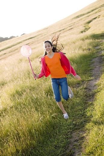 Hispanic girl running in field with net : Stock Photo