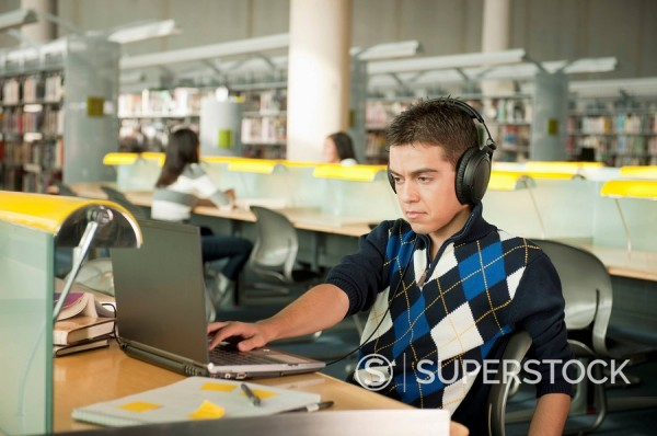Hispanic student listening to headphones and working at laptop in library : Stock Photo