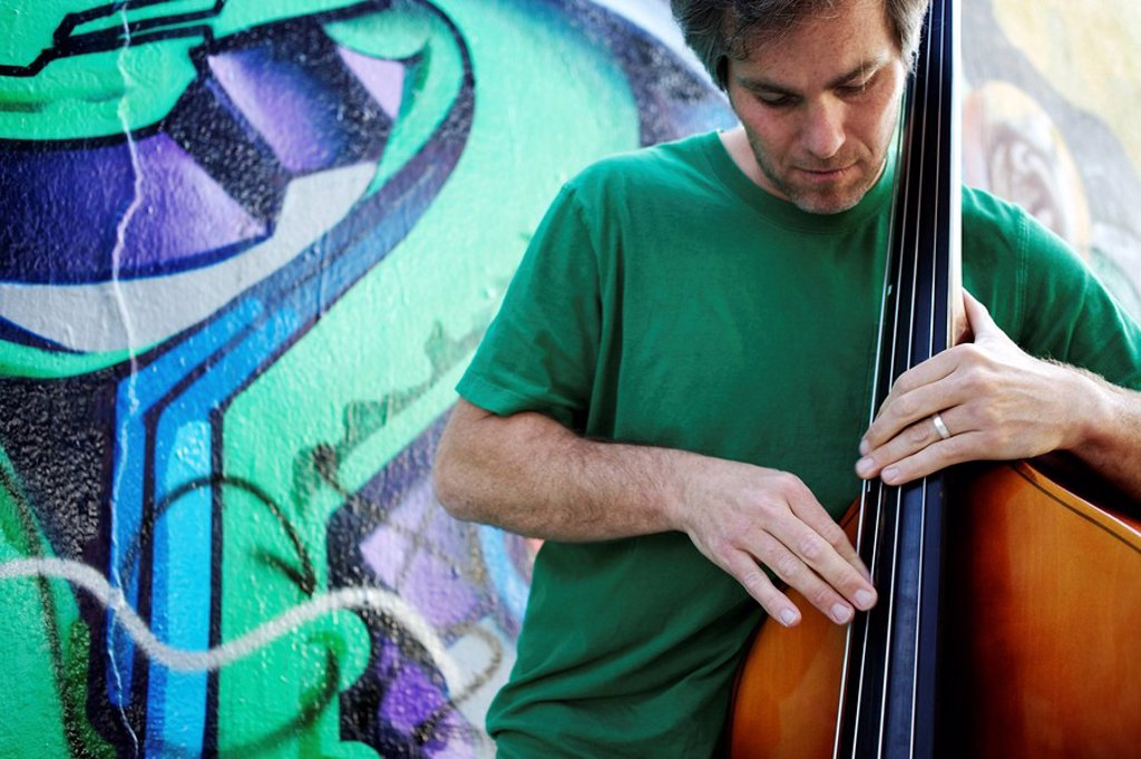Caucasian man playing double bass in front of graffiti covered wall : Stock Photo