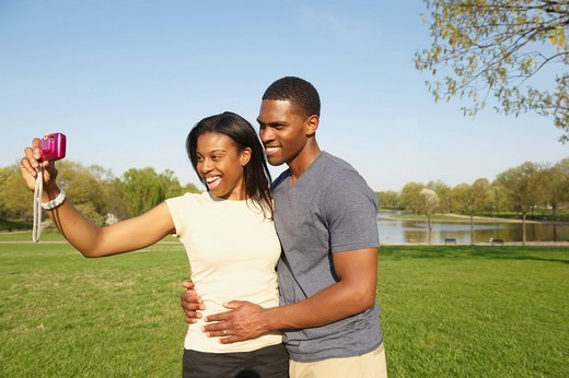 African American couple taking self_portrait in park : Stock Photo