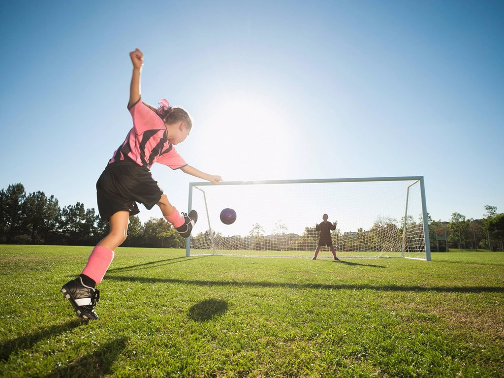 Stock Photo: 1589R-138322 Girl soccer player kicking soccer ball at net