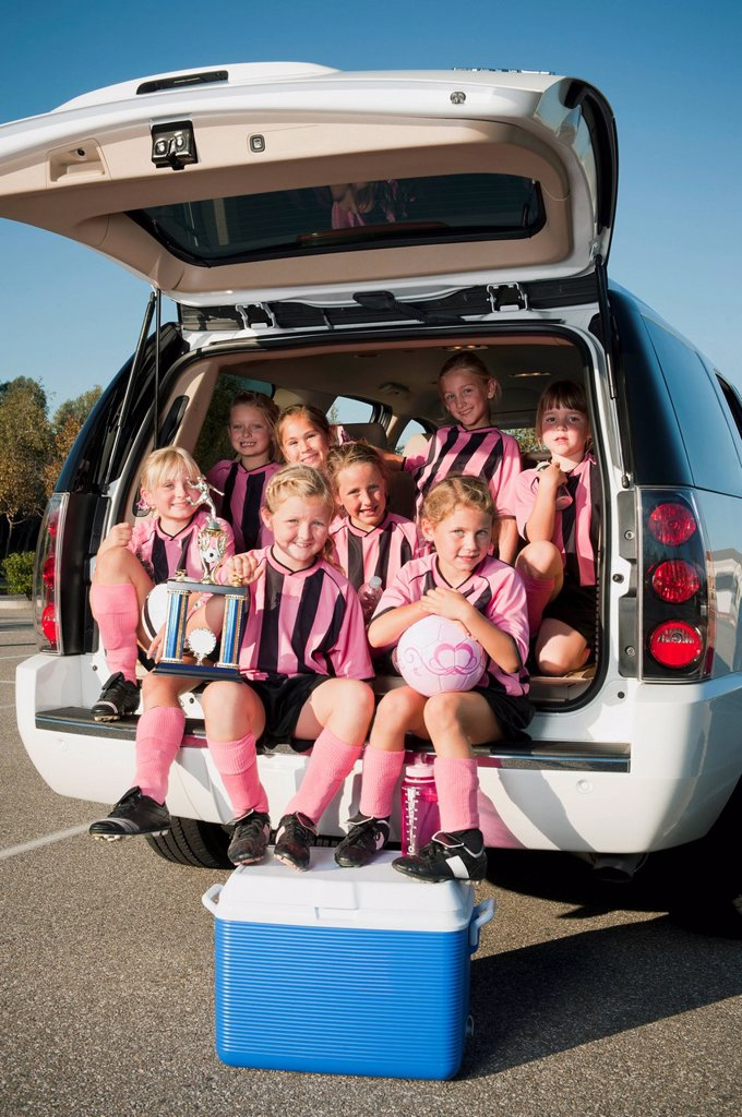 Stock Photo: 1589R-138333 Girl soccer players sitting in back of car with trophy