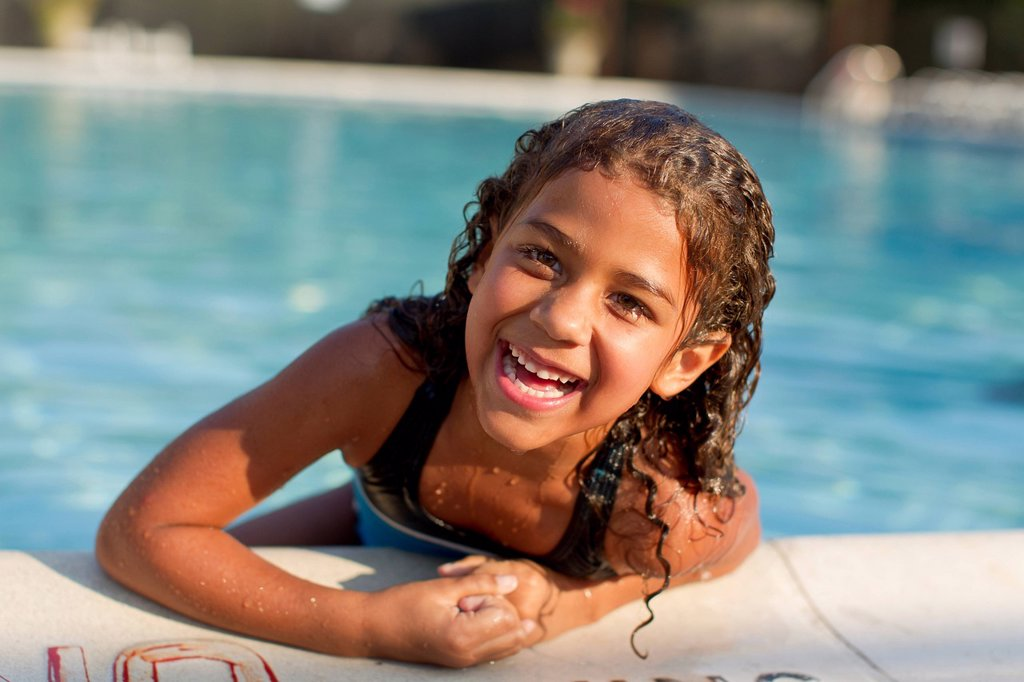 Mixed race girl swimming in swimming pool : Stock Photo