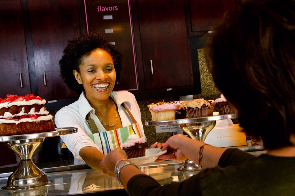 Stock Photo: 1589R-138356 African American bakery owner serving customer cupcake
