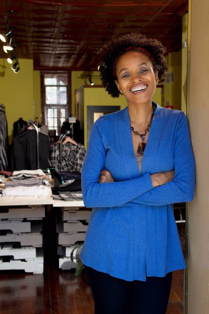 African American small business owner standing in clothing shop : Stock Photo