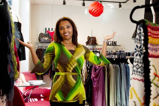 Mixed race small business owner standing in clothing shop : Stock Photo