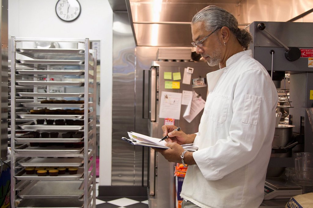 African American small business owner working in bakery kitchen : Stock Photo