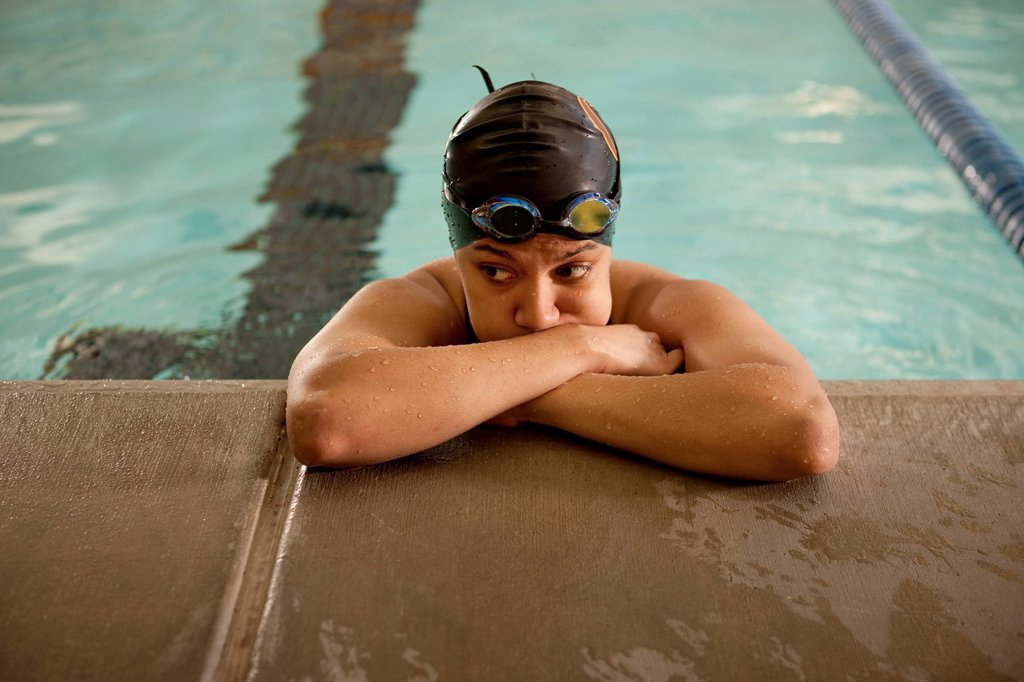 Unhappy Pacific Islander swimmer leaning at edge of pool : Stock Photo