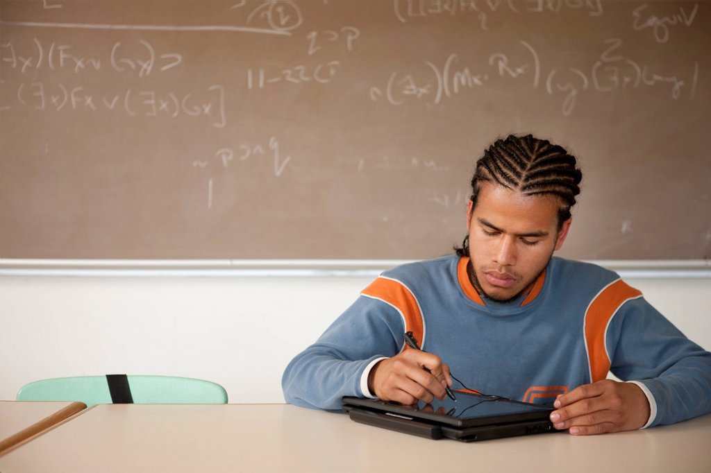 Stock Photo: 1589R-138622 Peruvian student studying in classroom on laptop