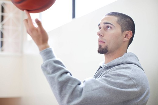 Hispanic man spinning basketball on finger : Stock Photo