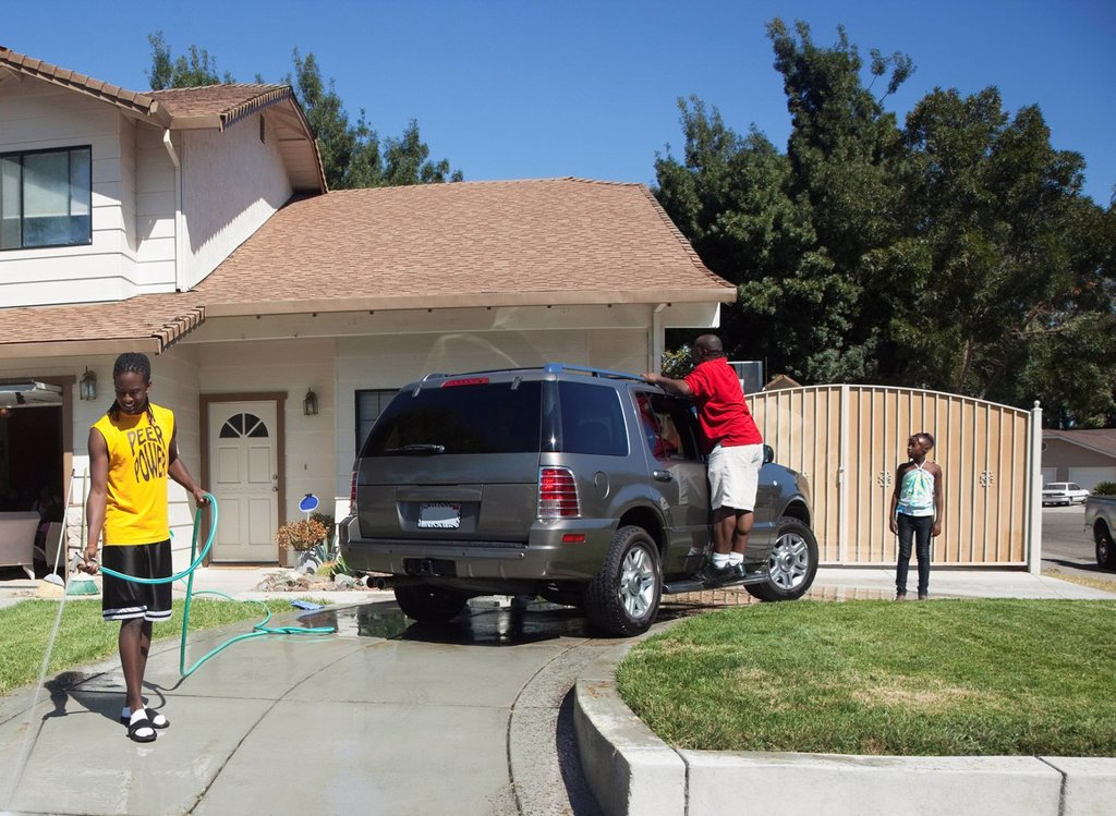 Black family washing car in driveway : Stock Photo