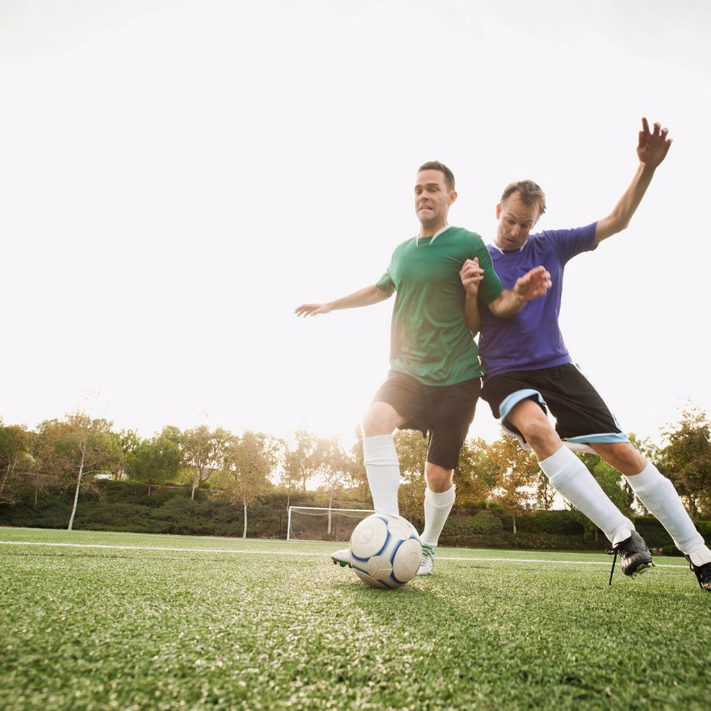 Men playing soccer on soccer field : Stock Photo