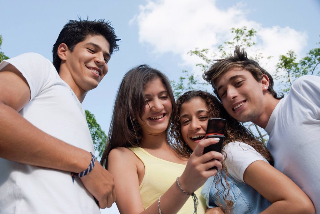 Hispanic friends looking at cell phone together : Stock Photo