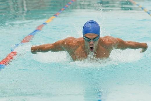 Hispanic man swimming in swimming pool : Stock Photo