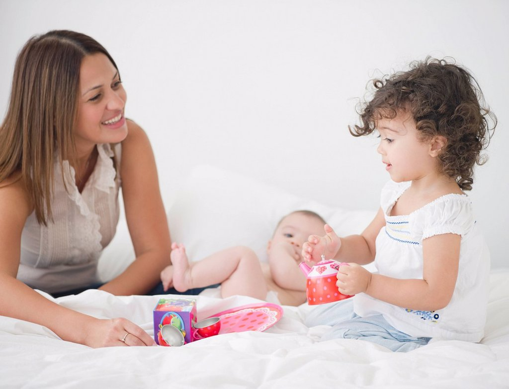Mother having tea party on bed with daughters : Stock Photo
