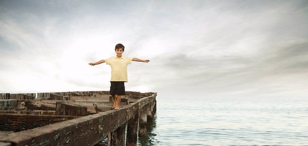 Stock Photo: 1589R-139396 Mixed race boy walking on dilapidated pier