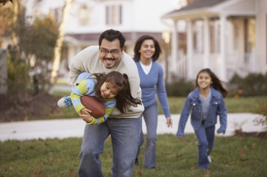 Stock Photo: 1589R-13944 Family playing football in front yard